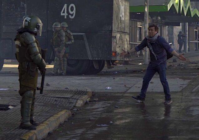 Manifestante frente a policía armada en Chile