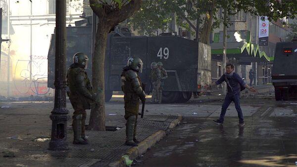 Manifestante frente a policía armada en Chile - Sputnik Mundo