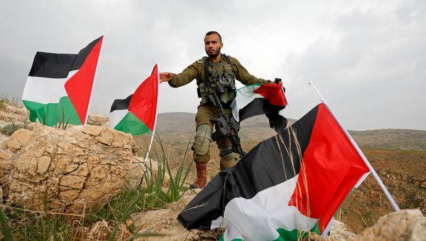 Un soldado israelí quita las banderas palestinas - Sputnik Mundo