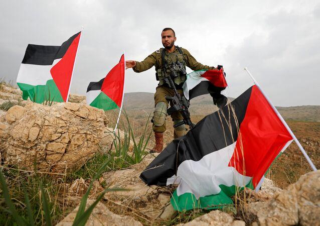 Un soldado israelí quita las banderas palestinas