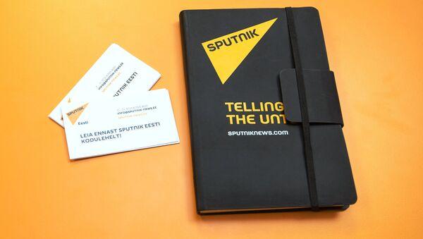 Un cuaderno con logo de Sputnik y tarjetas de visita de Sputnik Estonia - Sputnik Mundo