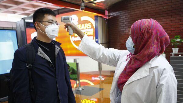 Un pasajero de Beijing es examinado para prevenir la infección por coronavirus en el aeropuerto de Dhaka, Bangladesh - Sputnik Mundo