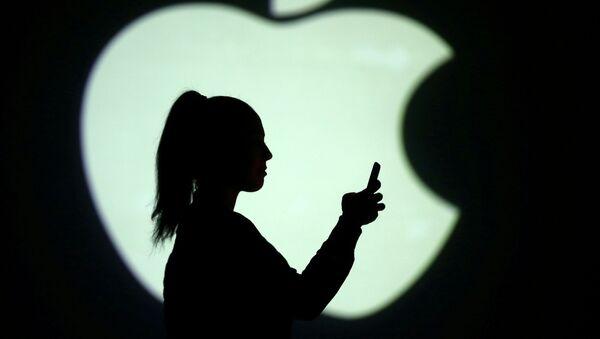 Una mujer con un dispositivo electrónico delante del logo de Apple - Sputnik Mundo