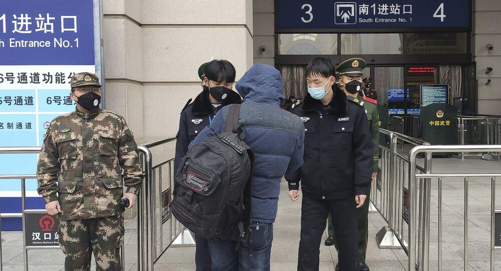 Funcionarios chinos con tapabocas controlan a los pasajeros en la Estación de Tren de Wuhan, tras la cuarentena por coronavirus
