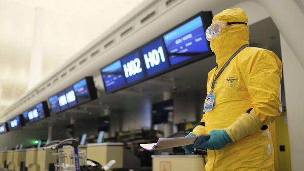 Работник в защитном костюме в аэропорту Уханя - Sputnik Mundo