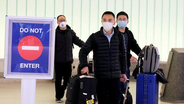 Unos chinos en mascarillas durante expansión del coronavirus  - Sputnik Mundo
