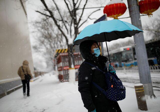 Mujer con mascarilla en Pekín