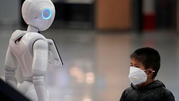 Un chico chino y un robot (imagen referencial) - Sputnik Mundo