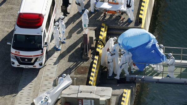 Сотрудники полиции в защитных костюмах помещают в машину скорой помощи заболевшего пассажира круизного лайнера Diamond Princes, помещенного в карантин у японского порта Йокогама - Sputnik Mundo