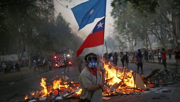 Manifestante con bandera de Chile y bandera mapuche en una barricada - Sputnik Mundo