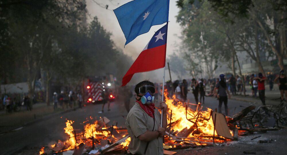 Manifestante con bandera de Chile y bandera mapuche en una barricada
