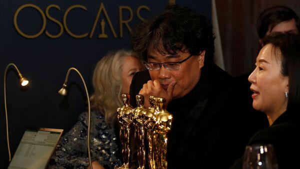 El director surcoreano Bong Joon-Ho mirando las estatuillas ganadas en la ceremonia de los Óscar 2020 - Sputnik Mundo