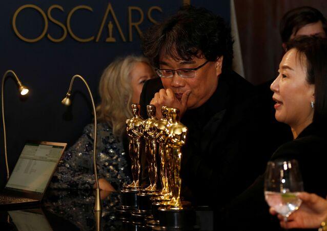 El director surcoreano Bong Joon-Ho mirando las estatuillas ganadas en la ceremonia de los Óscar 2020
