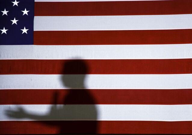 La bandera de EEUU y la sombra de un orador durante la campaña electoral de 2020