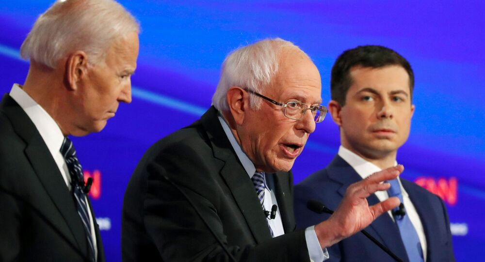 Joe Biden escucha a Bernie Sanders junto al exalcalde de South Bend Pete Buttigieg