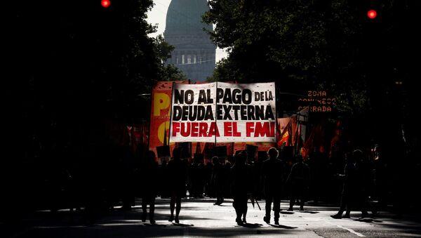 Manifestantes con un cartel en contra del FMI en Buenos Aires - Sputnik Mundo