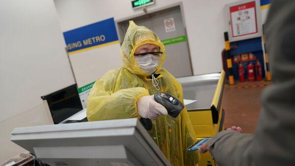 Un trabajador escanea el teléfono móvil de un cliente para el pago en un supermercado en Pekín - Sputnik Mundo
