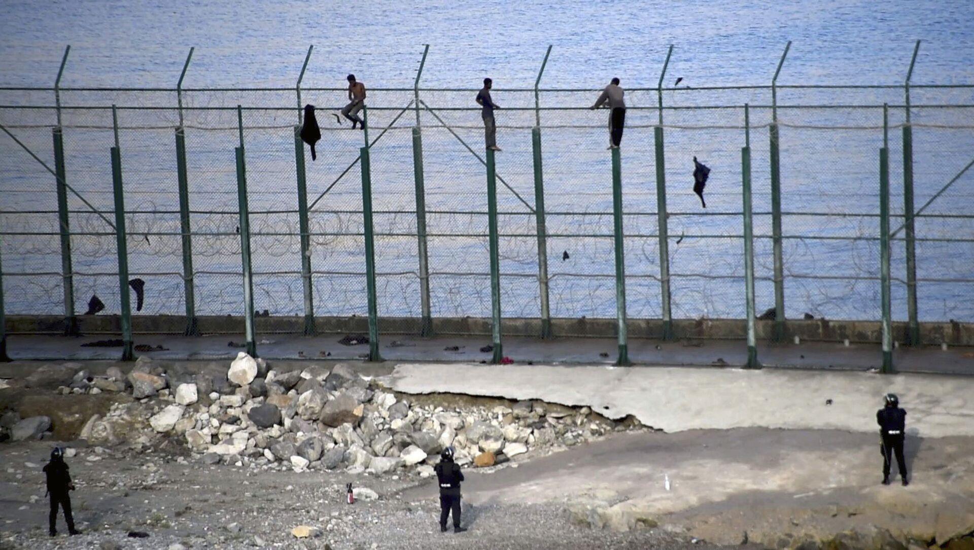 Migrantes en la valla fronteriza que separa la ciudad autónoma española de Ceuta de Marruecos - Sputnik Mundo, 1920, 27.05.2020