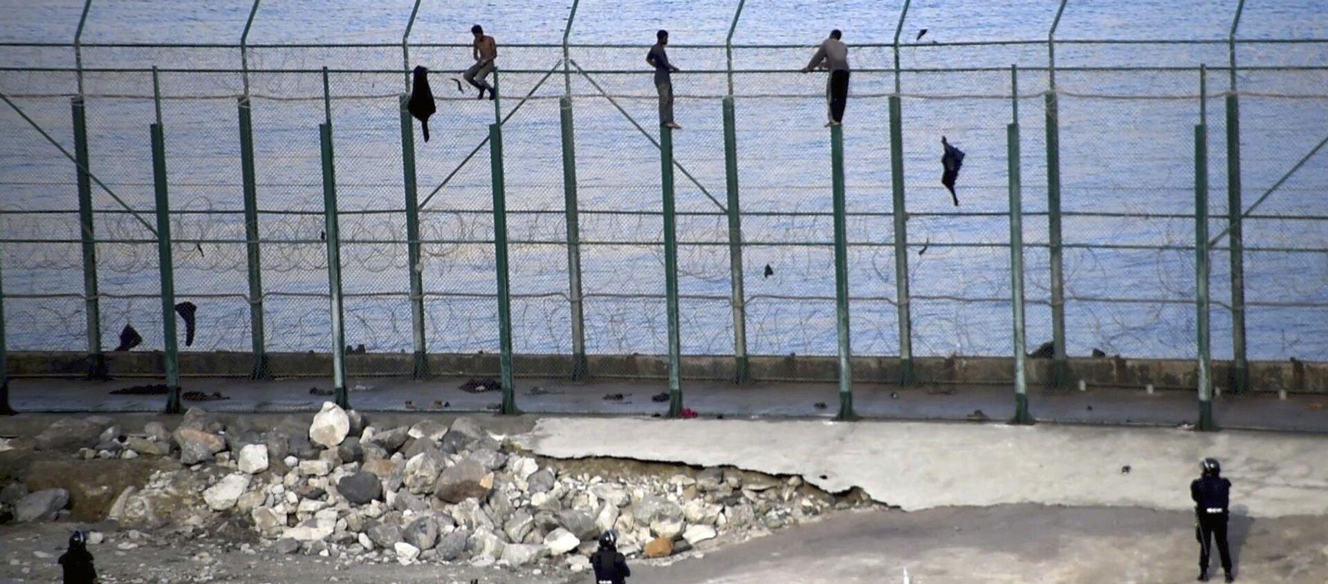 Migrantes en la valla fronteriza que separa la ciudad autónoma española de Ceuta de Marruecos - Sputnik Mundo, 1920, 23.12.2020