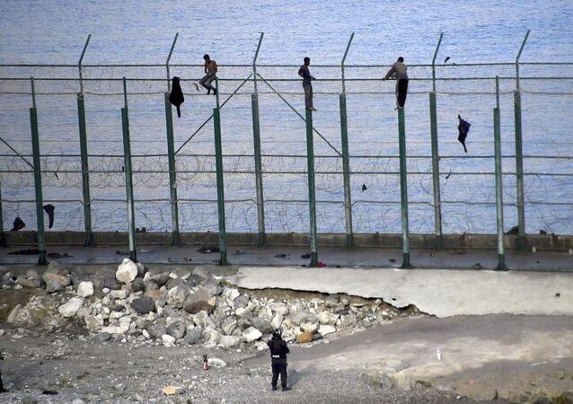 Migrantes en la valla fronteriza que separa la ciudad autónoma española de Ceuta de Marruecos
