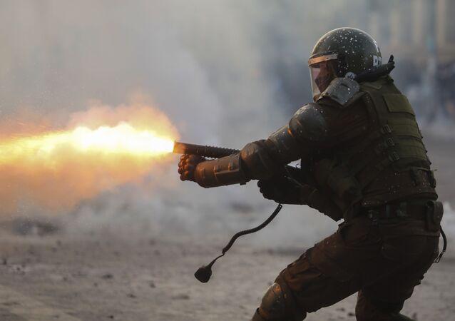 Policía chileno disparando bomba lacrimógena