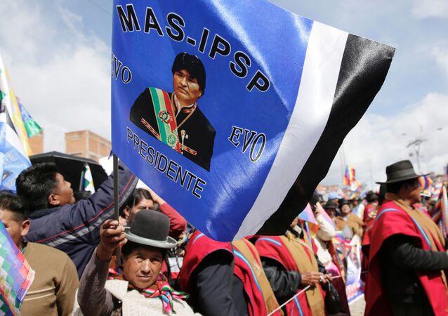 Simpatizantes del Movimiento Al Socialismo con una bandera de Evo Morales