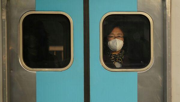 Una mujer surcoreanana con un tapabocas - Sputnik Mundo