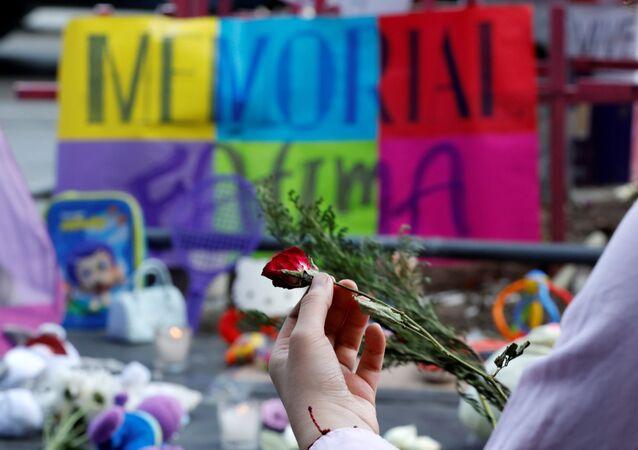 Una persona con una flor en homenaje a la niña asesinada