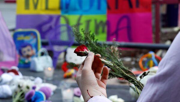 Una persona con una flor en homenaje a la niña asesinada - Sputnik Mundo