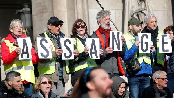 Manifestantes sostienen las letras del apellido de Julian Assange - Sputnik Mundo