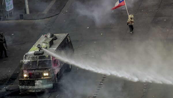 Carro lanzaguas durante las protestas en Chile - Sputnik Mundo