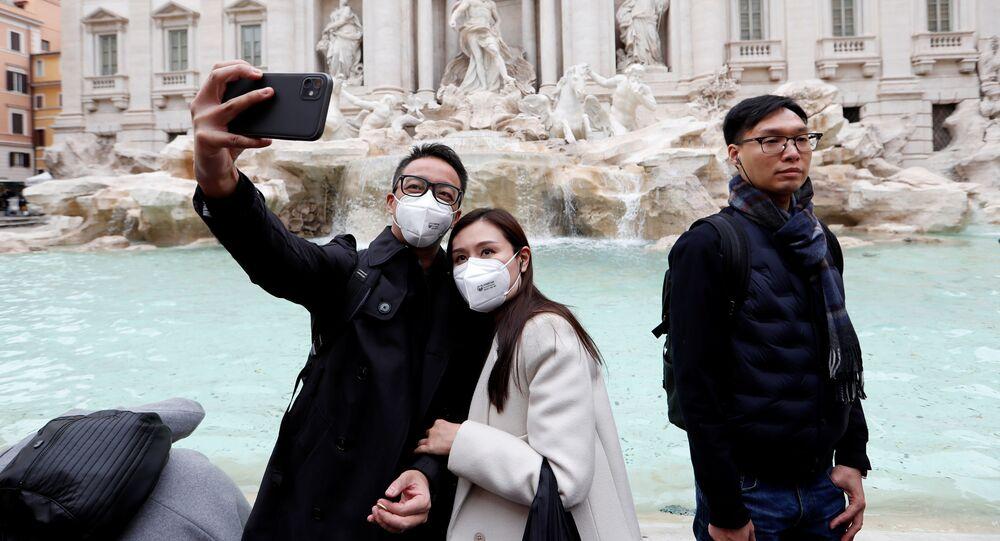 Turistas con tapabocas sacan un selfie en Roma, Italia