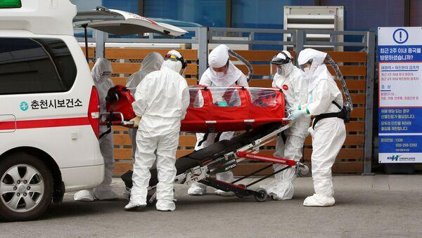 Médicos en Corea del Sur atienden a una persona contagiada con el coronavirus - Sputnik Mundo