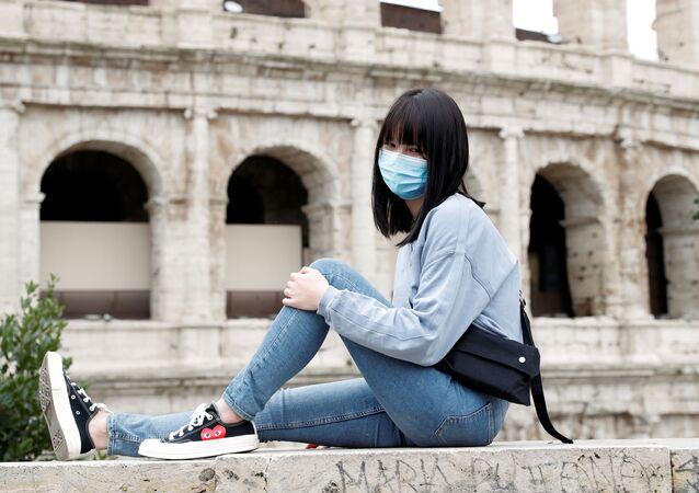 Una chica con mascarilla posa en el Coliseo