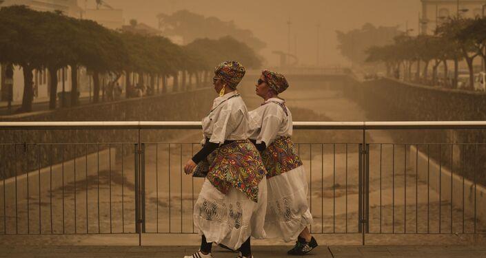 Dos personas con disfraces de carnaval caminan en Santa Cruz de Tenerife en medio de tormenta de arena roja