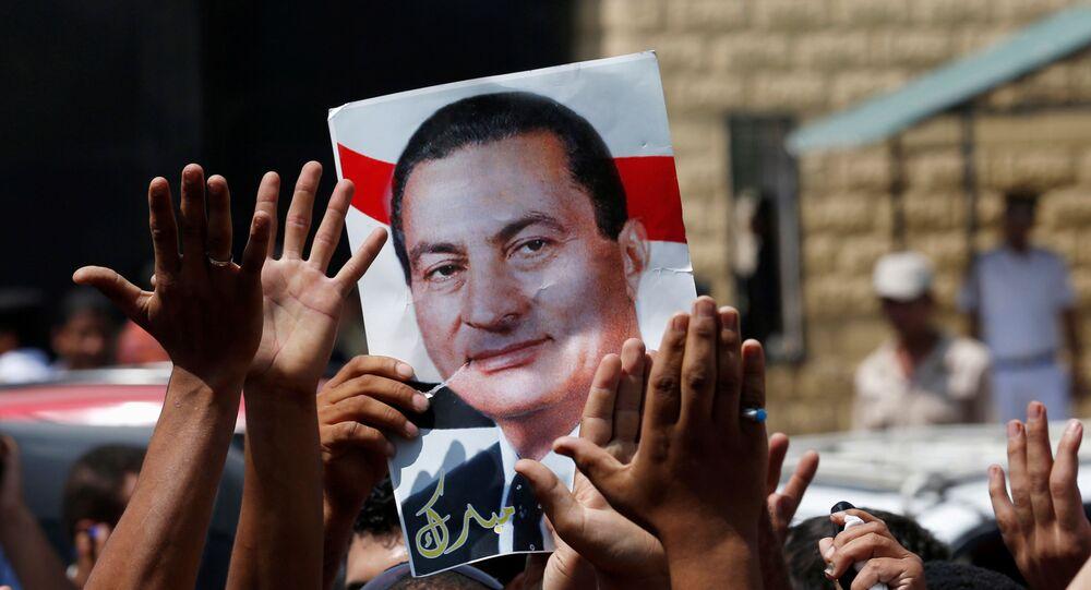 Los partidarios de Hosni Mubarak sostienen su cartel para celebrar su liberación frente a la puerta principal de la prisión de Tora, en las afueras de El Cairo