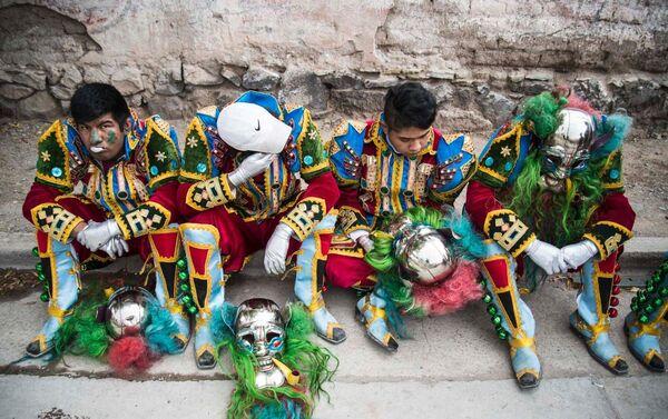 Jóvenes con trajes típicos de Carnaval tomando un descanso en una acera. - Sputnik Mundo