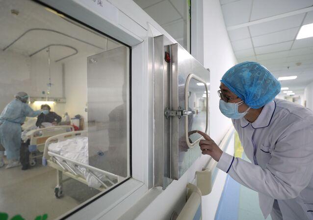 Un médico en un hospital observa la asistencia del personal a pacientes con coronavirus
