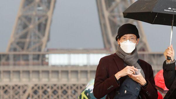 Una persona con mascarilla frente a la Torre Eiffel en París, Francia - Sputnik Mundo