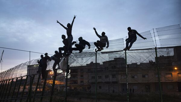 Inmigrantes subsaharianos trepan por la valla de Melilla - Sputnik Mundo