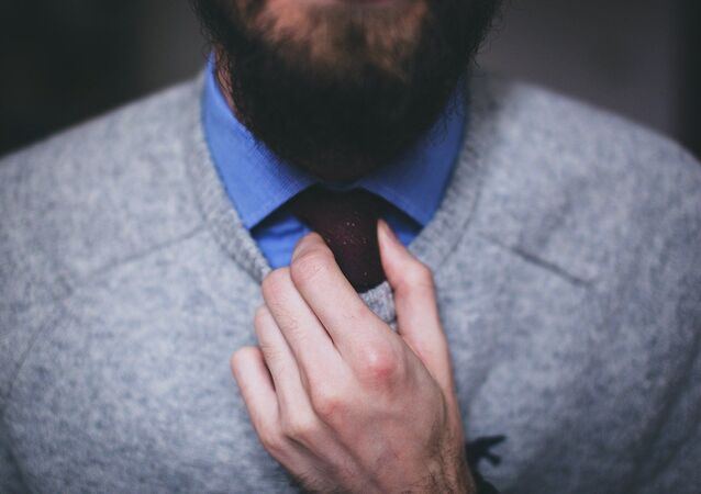 Un hombre con barba ajusta su corbata