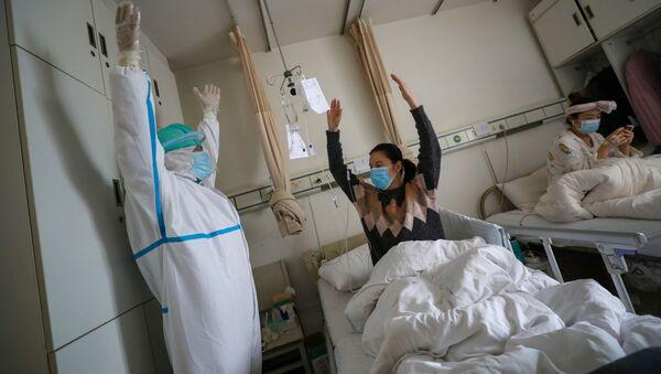 Un médico junto a una paciente en un hospital de Wuhan, China - Sputnik Mundo