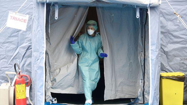 Personal médico en un traje protector y una mascarilla - Sputnik Mundo
