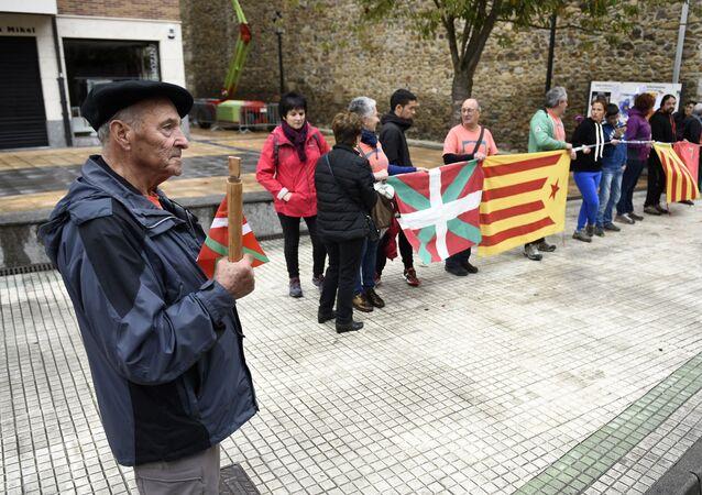 Un señor sostiene un bastón con la bandera vasca al lado de personas que llevan la catalana