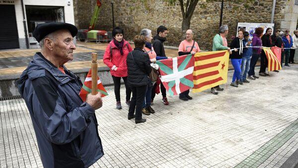Un señor sostiene un bastón con la bandera vasca al lado de personas que llevan la catalana - Sputnik Mundo