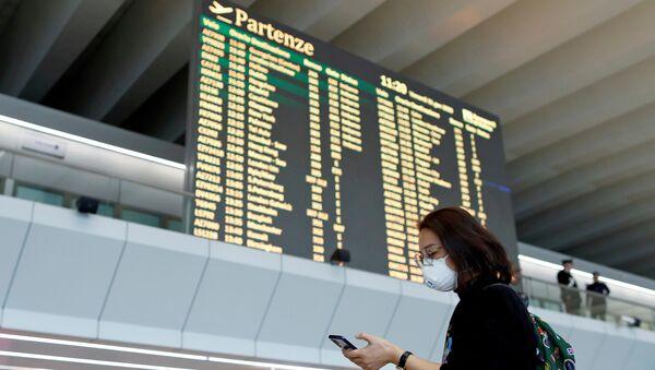 Una chica con mascarilla durante el brote de coronavirus en el aeropuerto de Roma, Italia - Sputnik Mundo