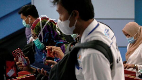La gente con mascarillas debido al nuevo coronavirus - Sputnik Mundo