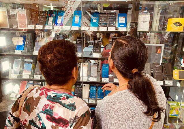 Dos mujeres miran un expositor de celulares en una tienda de Caracas