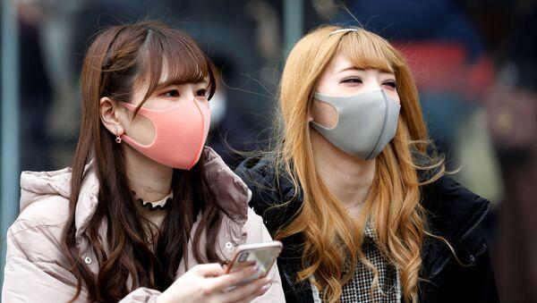Chicas en mascarillas en las calles de Tokio - Sputnik Mundo