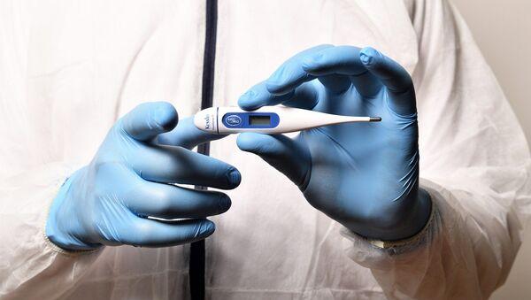 Una persona con un termómetro. Fiebre, gripe, coronavirus. Imagen referencial - Sputnik Mundo